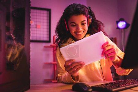 Lächelnder afrikanisch-amerikanischer Spieler im Headset-Gaming auf digitalem Tablet in der Nähe des Computers im verschwommenen Vordergrund