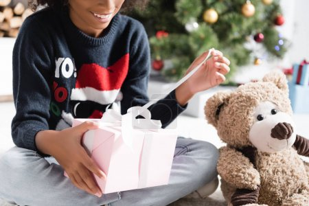 cropped view of happy african american girl opening christmas present on blurred background