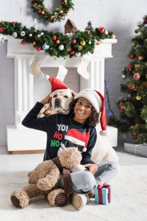 Photo for Happy african american girl sitting on floor with teddy bear and hugging labrador dog on blurred background - Royalty Free Image