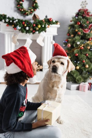african american girl in santa hat holding gift box while sitting near labrador dog on blurred background
