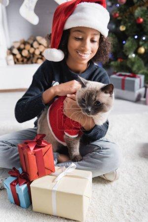 Photo pour Gai afro-américaine fille dans santa chapeau câlins moelleux chat tandis que assis près de cadeaux de Noël sur fond flou - image libre de droit