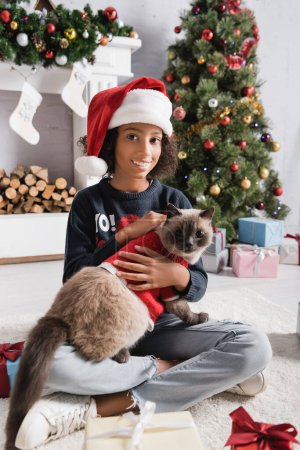 happy african american girl smiling at camera while cuddling cat near christmas tree on blurred background