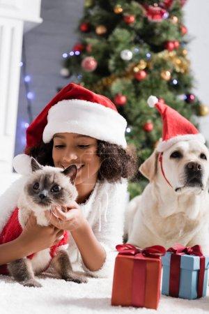 heureux afro-américaine fille dans santa chapeau câlin chat tout couché sur le sol près de labrador chien sur fond flou