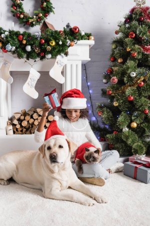 happy african american girl holding gift box while sitting with dog and cat near christmas tree and fireplace