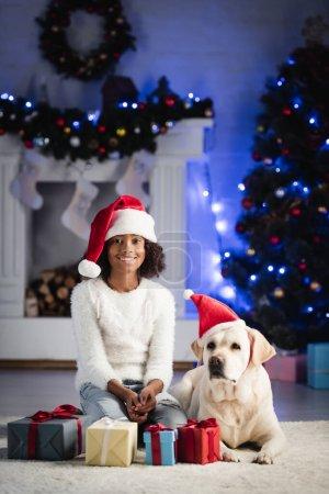 Photo pour Labrador dans santa chapeau, couché près souriant afro-américaine fille assise près de boîtes-cadeaux sur fond flou - image libre de droit