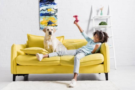 KYIV, UKRAINE - OCTOBER 02, 2020: cheerful curly girl with pink joystick lying on sofa near retriever at home
