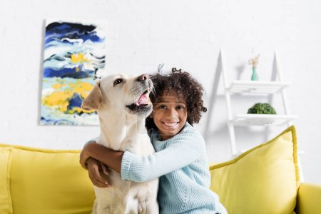 Photo for Happy curly girl embracing labrador barking, while sitting on yellow sofa at home - Royalty Free Image