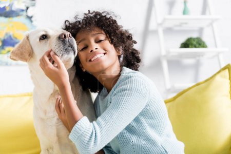 Photo for Smiling african american girl leaning on retriever, while sitting on yellow sofa at home, on blurred background - Royalty Free Image