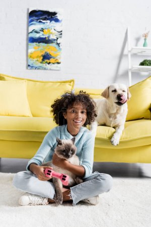 Photo for KYIV, UKRAINE - OCTOBER 02, 2020: happy african american girl with joystick embracing cat near dog lying on sofa at home - Royalty Free Image