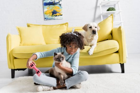 Photo for KYIV, UKRAINE - OCTOBER 02, 2020: Preteen girl with joystick embracing cat, while sitting near dog at home - Royalty Free Image