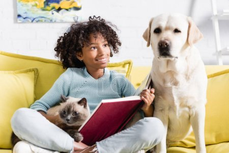 Photo for African american girl with open book, embracing cat, while looking at labrador sitting on sofa at home on blurred background - Royalty Free Image