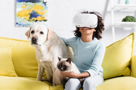 Photo for Smiling african american girl in vr headset sitting near retriever and cat on sofa at home, on blurred background - Royalty Free Image