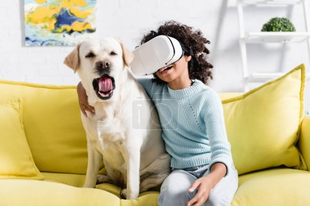 Photo pour Fille afro-américaine bouclée dans un casque vr embrassant chien bâillant, tout en étant assis sur un canapé sur fond flou - image libre de droit