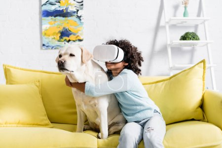 Photo for Smiling african american girl in vr headset embracing dog, while sitting on yellow sofa at home - Royalty Free Image