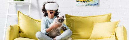 Photo for African american girl with open mouth in vr headset embracing cat, while sitting on sofa at home, banner - Royalty Free Image