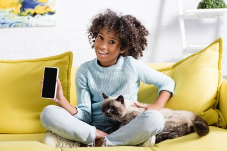Photo for African american girl holding cellphone with blank screen, while stroking cat, sitting on sofa on blurred background - Royalty Free Image
