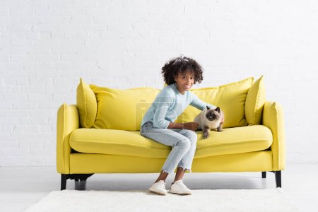 Photo for Smiling african american girl embracing siamese cat, while sitting on sofa at home - Royalty Free Image