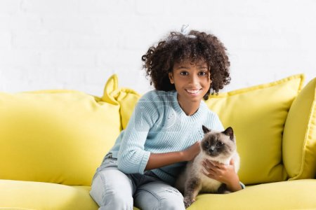 Photo for Happy african american girl stroking siamese cat, while sitting on sofa at home - Royalty Free Image