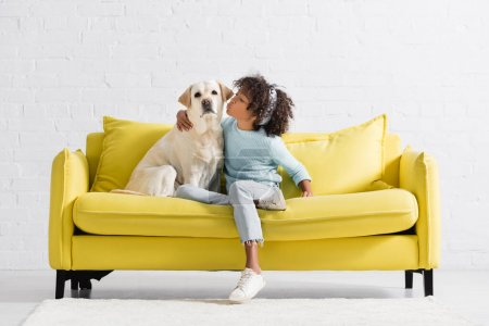 Photo for African american girl kissing and embracing retriever looking at camera, while sitting on sofa at home - Royalty Free Image
