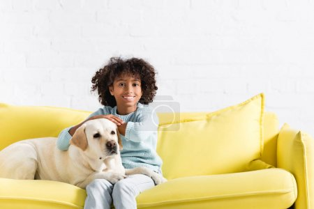 Photo for Cheerful african american girl looking at camera, while leaning on retriever looking away on yellow sofa at home - Royalty Free Image