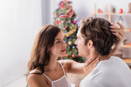woman hugging boyfriend with decorated christmas tree on blurred background