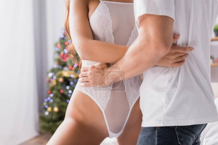 cropped view of passionate man hugging seductive girlfriend in bodysuit with decorated christmas tree on blurred background