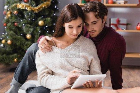 Photo pour Couple en chandails en utilisant une tablette numérique près de l'arbre de Noël sur fond flou - image libre de droit