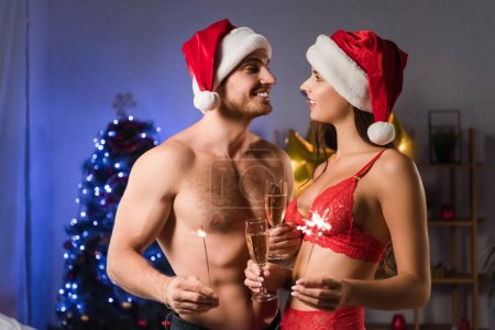 Photo for Happy and sexy couple in santa hats holding glasses with champagne and sparklers near blurred lighting on christmas tree - Royalty Free Image