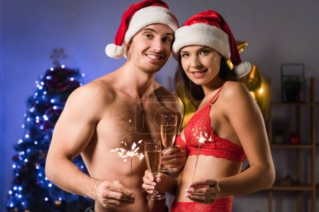 Photo for Happy and sexy couple in santa hats holding glasses with champagne and sparklers near blurred lighting - Royalty Free Image