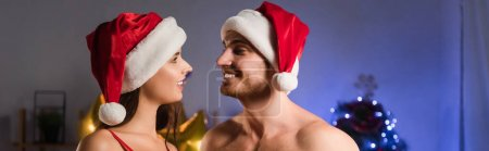 Photo for Cheerful couple in santa hats looking at each other, banner - Royalty Free Image