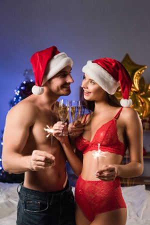 Photo for Happy and sexy couple in santa hats clinking glasses with champagne and holding sparklers near blurred lighting - Royalty Free Image