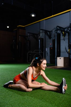smiling sportswoman reaching sneaker while doing stretching exercise in sport center