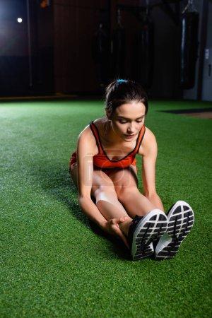 Photo pour Sportive en soutien-gorge et baskets faire assis exercice de flexion vers l'avant sur le tapis dans le centre de sport - image libre de droit
