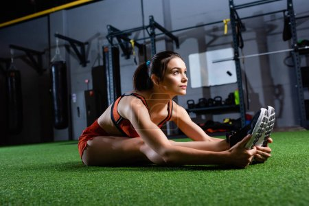young sportswoman looking away while doing seated forward bend exercise in gym