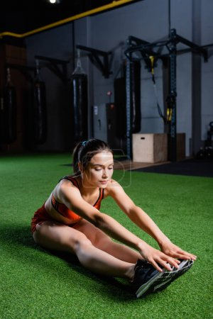 Sportlerin greift mit den Händen nach Turnschuhen bei sitzender Vorwärtsbeugeübung