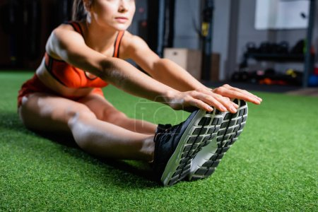 cropped view of sportswoman touching sneakers while doing seated forward bend exercise in gym, blurred background