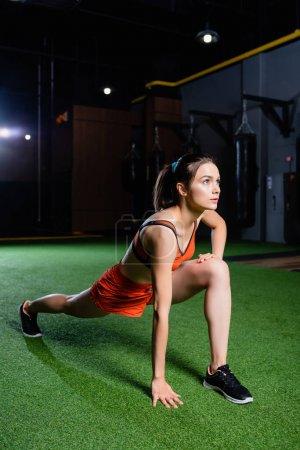 Photo pour Jeune sportive faisant de l'exercice en avant fend tout échauffement dans la salle de gym - image libre de droit