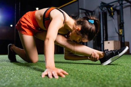 Photo pour Sportive atteignant la jambe avec la tête tout en s'étirant dans la salle de gym sur le premier plan flou - image libre de droit
