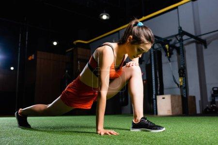Photo pour Sportive sportive faisant avancer l'exercice tout en se réchauffant dans la salle de gym - image libre de droit