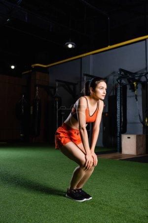 junge Sportlerin in kurzen Hosen und Sport-BH schaut beim Aufwärmen im Fitnessstudio weg