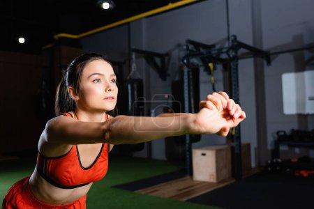 Photo pour Jeune sportive étirant les bras tout en regardant loin dans la salle de gym - image libre de droit