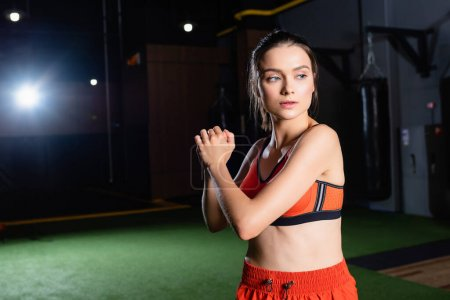athletic sportswoman looking away while warming up arms in gym