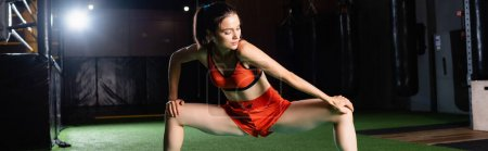 athletic sportswoman stretching legs while training in gym, banner