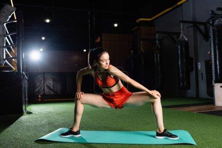 mujer deportiva en pantalones cortos y piernas de estiramiento superior mientras hace ejercicio en el centro deportivo