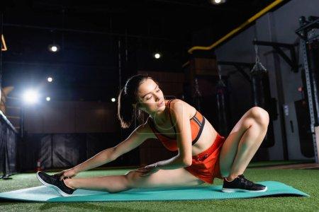 Photo pour Femme sportive faisant assis côté plier l'exercice tout en s'étirant dans le centre sportif - image libre de droit