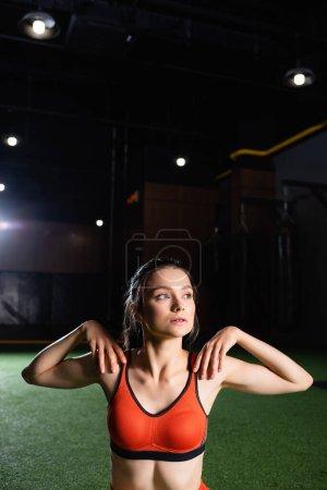 Photo pour Sportive regardant loin tout en réchauffant les bras et les épaules dans la salle de gym - image libre de droit