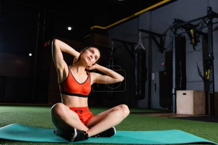 sportive woman in sports bra and shorts sitting on fitness mat with crossed legs and warming up neck