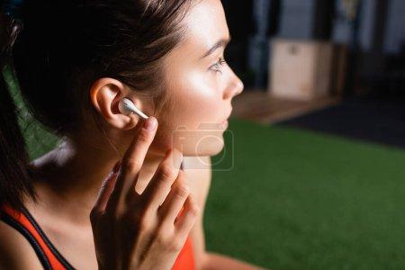 junge Sportlerin berührt drahtlosen Kopfhörer und schaut im Sportzentrum weg