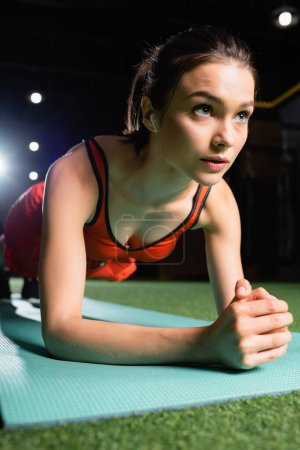 sportswoman with earphone doing plank exercise while training in gym