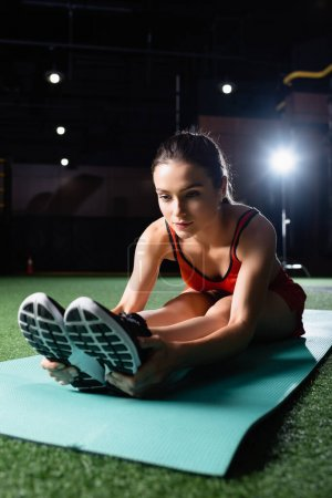 Photo for Young sportive woman touching sneakers while doing seated forward bend exercise - Royalty Free Image